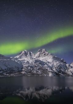 Verticale opname van de weerspiegeling van een besneeuwde bergen in het water onder het noorderlicht
