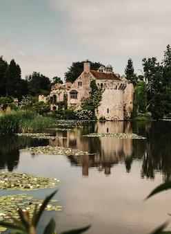 Verticale opname van de weerspiegeling van een oud kasteel op een prachtige vijver omgeven door bomen