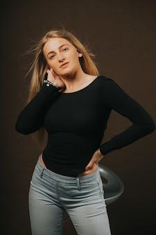 Verticale opname van een aantrekkelijke blonde vrouw die poseert terwijl ze op een barkruk zit