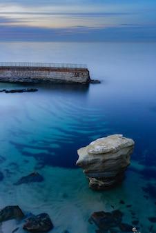 Verticale opname van een adembenemende blauwe en heldere zee met een stenen hek