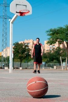 Verticale opname van een bal op een basketbalveld met een spelende man
