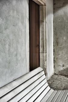 Verticale opname van een bankje in de tuin naast de deur van een oud woonhuis