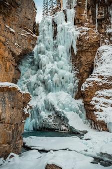 Verticale opname van een bevroren waterval, omringd door rotsformaties