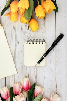 Verticale opname van een blanco notitieboekje en een pen, enkele bloemen op een houten oppervlak