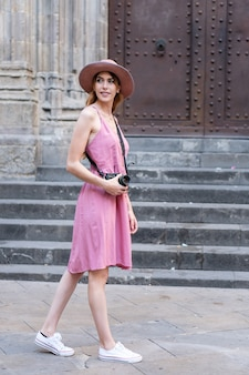 Verticale opname van een blanke blonde mooie toerist met een hoed die foto's van de stad maakt