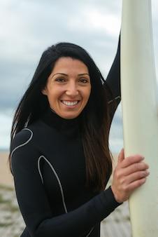 Verticale opname van een blanke vrouw die een surfpak draagt met een surfplank die vrolijk lacht