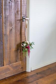 Verticale opname van een bloemdecoratie die aan de deurklink hangt
