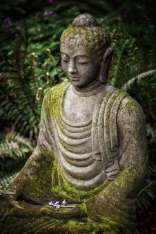Verticale opname van een boeddhabeeld met mos erop en groen in de verte
