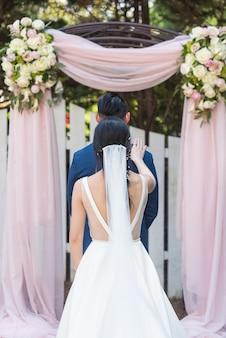 Verticale opname van een bruid en een bruidegom die poseren in een park