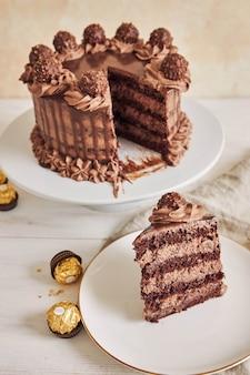 Verticale opname van een chocoladetaart en een plakje op een bord naast wat stukjes chocolade pieces