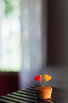 Verticale opname van een cupcake met kleurrijke hartjes erop