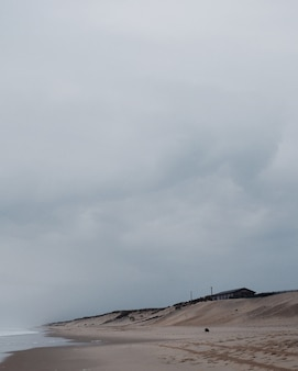 Verticale opname van een eenzaam huis aan het strand onder de bewolkte hemel