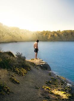 Verticale opname van een eenzaam mannetje dat zich klaarmaakt om op een zonnige dag in het meer te springen