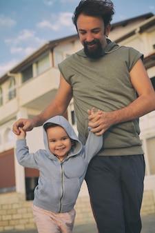 Verticale opname van een gelukkige vader die de handen van zijn dochter vasthoudt