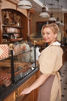 Verticale opname van een gelukkige volwassen vrouw die geniet van het werken in haar bakkerijwinkel en vers brood en gebak verkoopt