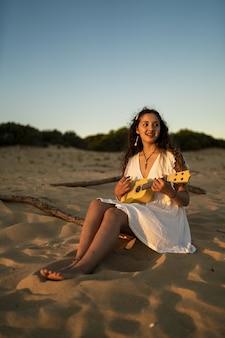 Verticale opname van een glimlachende vrouw in een witte jurk, zittend op een zanderige grond