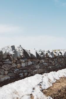 Verticale opname van een grijze stenen muur onder een heldere blauwe hemel