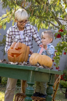 Verticale opname van een grootmoeder die een kind helpt pompoenen voor halloween te snijden