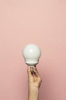 Verticale opname van een hand met een gloeilamp geïsoleerd op een roze muur