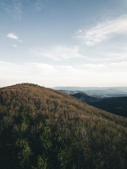 Verticale opname van een heuvel onder de bewolkte blauwe hemel overdag