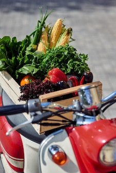 Verticale opname van een houten kist met verse groenten op een scooter die op de stad staat