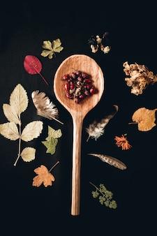 Verticale opname van een houten lepel omringd met bladeren en veren van verschillende planten
