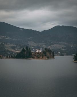 Verticale opname van een huis aan de kust, omgeven door bomen en bergen