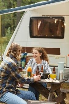 Verticale opname van een jong stel dat buiten geniet van een picknick tijdens het kamperen met kopieerruimte voor een aanhangwagen