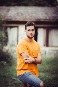 Verticale opname van een jonge blanke man met blond haar in een oranje shirt