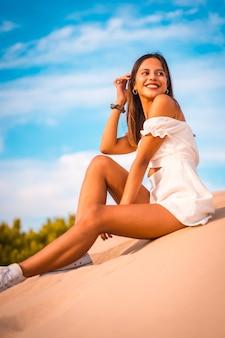 Verticale opname van een jonge brunette blanke vrouw die geniet van een vakantie op het strand in een witte jurk