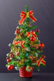 Verticale opname van een kerstboom versierd met rode linten en ballen