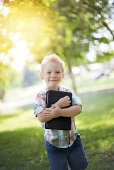 Verticale opname van een kind dat de bijbel tegen zijn borst houdt terwijl hij naar de camera kijkt