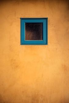 Verticale opname van een klein blauw raam op een houten deur