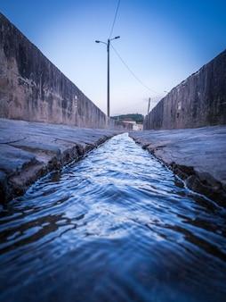 Verticale opname van een klein kanaal door betonnen muren aan beide zijden