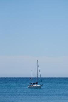 Verticale opname van een kleine boot die in de oceaan vaart met een heldere blauwe lucht