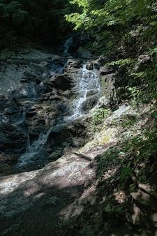 Verticale opname van een kleine watervallen in het bos