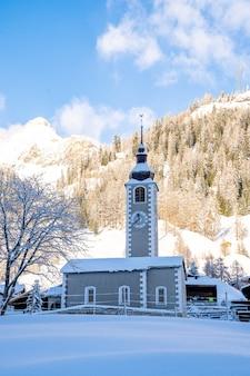 Verticale opname van een klokkentoren met besneeuwde bergen