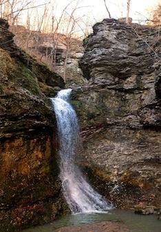 Verticale opname van een krachtige waterval die door rotsen in een bos stroomt