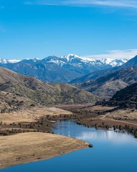Verticale opname van een kronkelende rivier met majestueuze bergen en blauwe lucht
