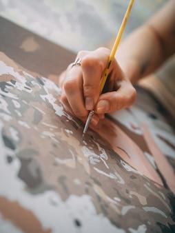 Verticale opname van een kunstenaar die op het canvas schildert