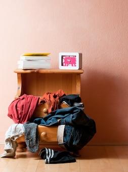 Verticale opname van een lade met verschillende kleren erop, samen met boeken en een klok