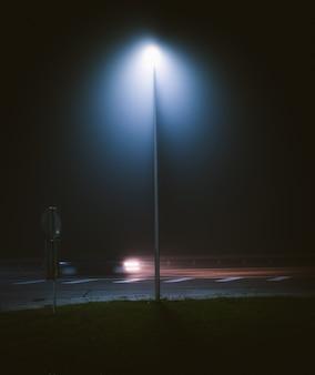 Verticale opname van een lantaarnpaal bij de straat, vastgelegd tijdens de nacht