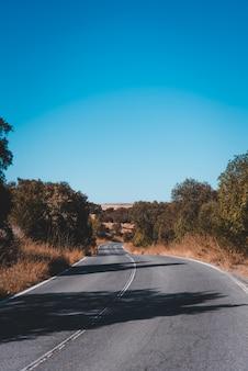 Verticale opname van een lege weg op een zonnige dag