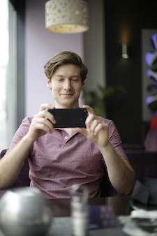Verticale opname van een man die een foto neemt met zijn telefoon