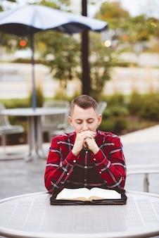 Verticale opname van een man die een rood shirt draagt en aan een tafel zit met een open boek in de vorm van hem