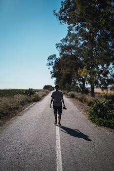 Verticale opname van een man met een camera die midden op een lege weg met bomen aan de zijkant loopt