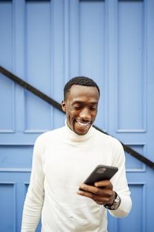 Verticale opname van een man met een coltrui die naar zijn telefoon kijkt