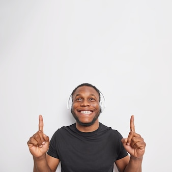 Verticale opname van een man met een positieve baard wijst naar boven met beide wijsvingers