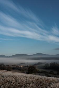 Verticale opname van een mistig veld en bergen met een blauwe lucht op de achtergrond