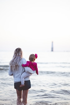 Verticale opname van een moeder die haar baby vasthoudt en naar de horizon van de zee kijkt
